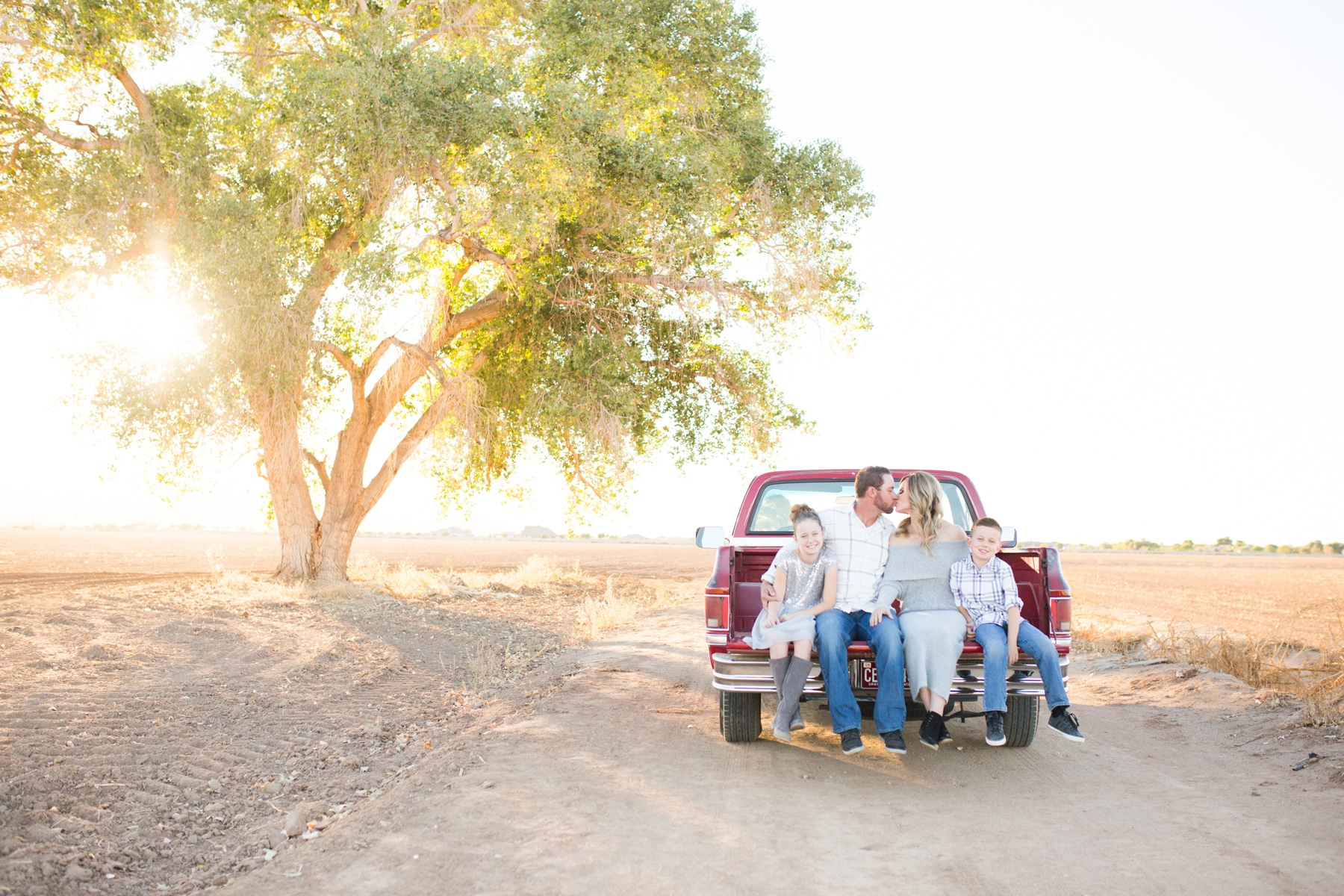 Family photos in old truck under tree at sunset