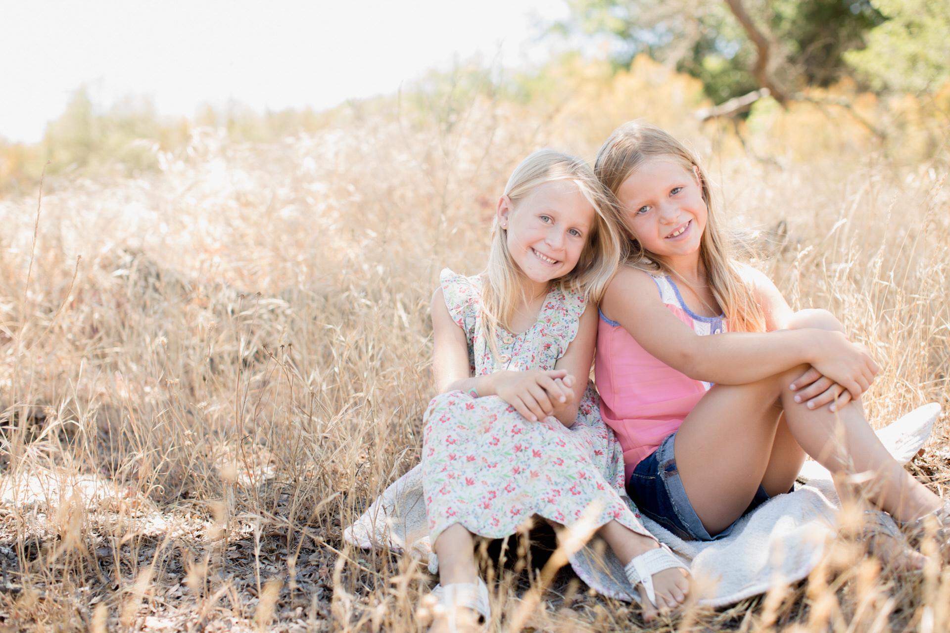 Sisters sitting in grass field
