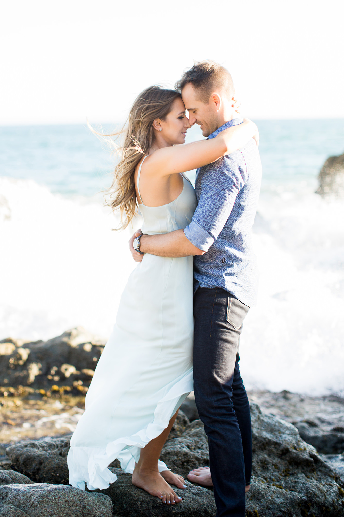 engagement photos on beach with wave crashing behind couple