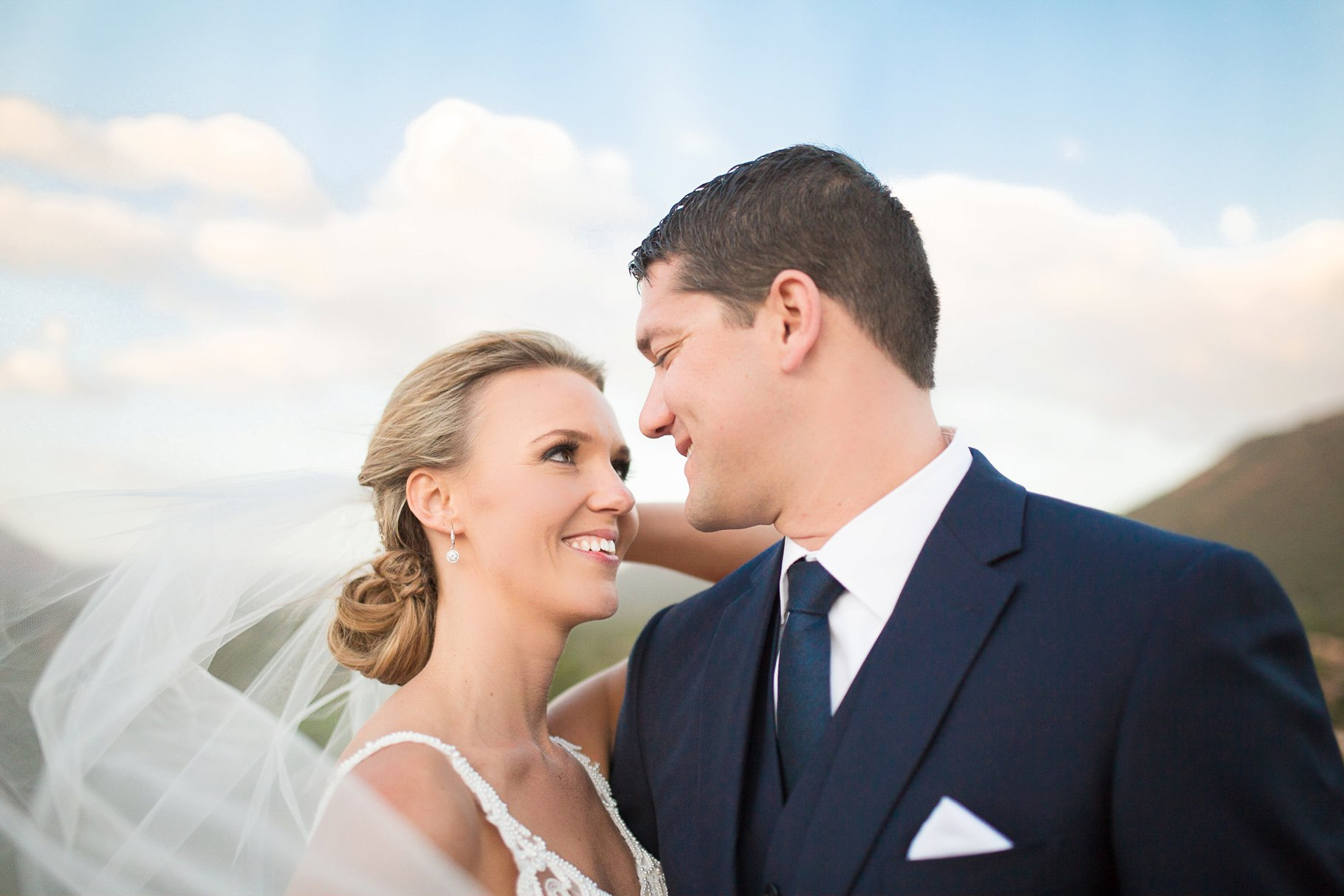 wind blowing brides veil with Sedona in backdrop