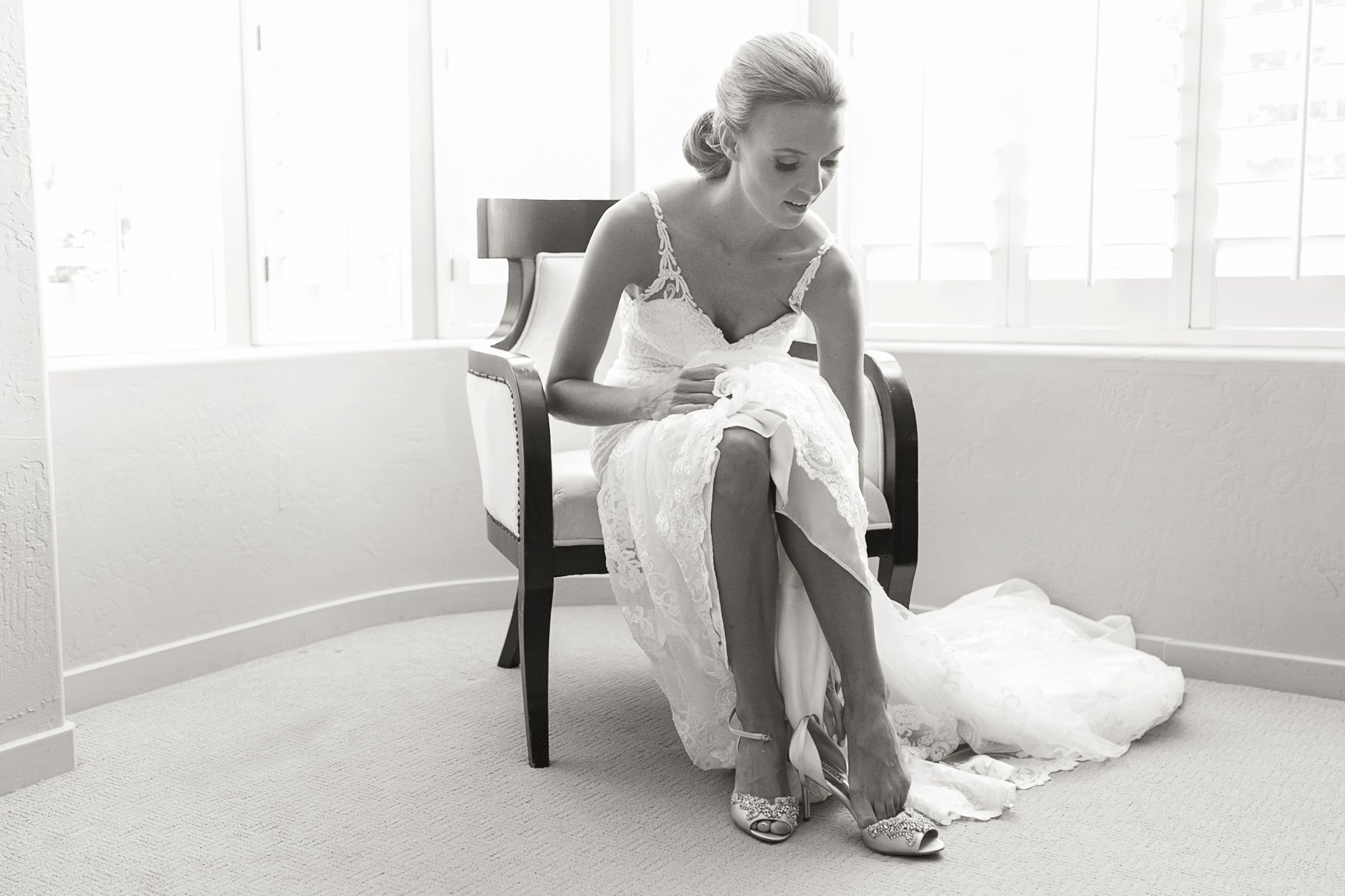 Black and white image of bride putting on shoes