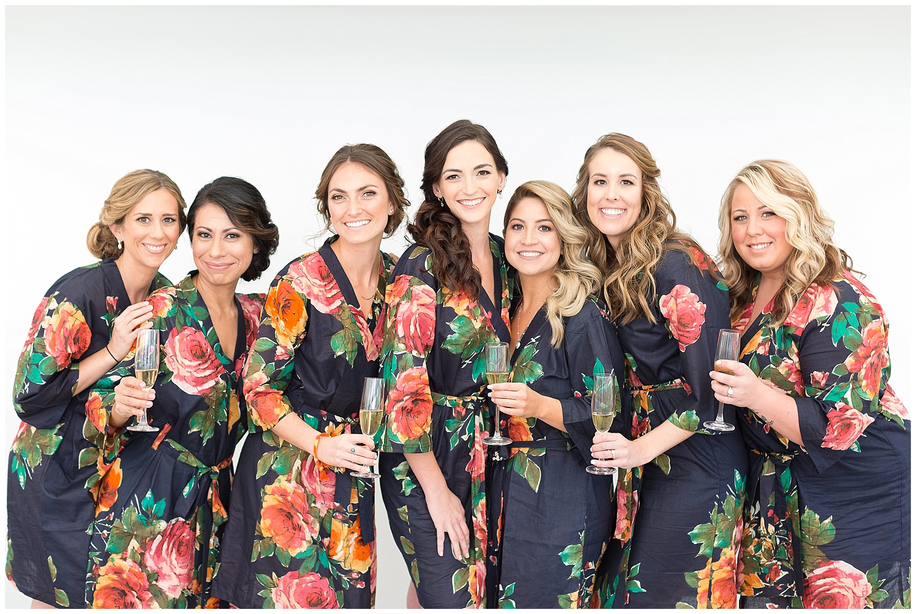 Bridesmaids in floral robes with champagne