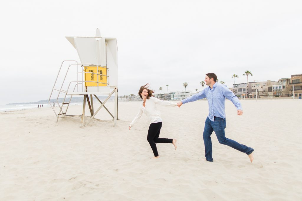 Mission Beach Engagement Session with Couple running on beach