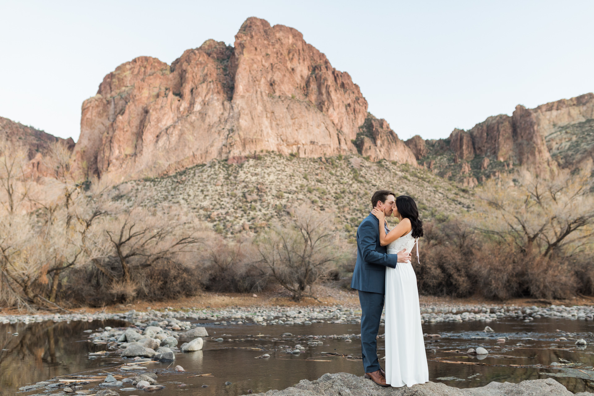bride and groom kissing at river with mountain in backdrop