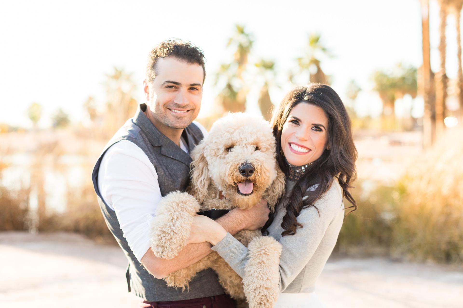 Engaged couple holding a labradoodle dog