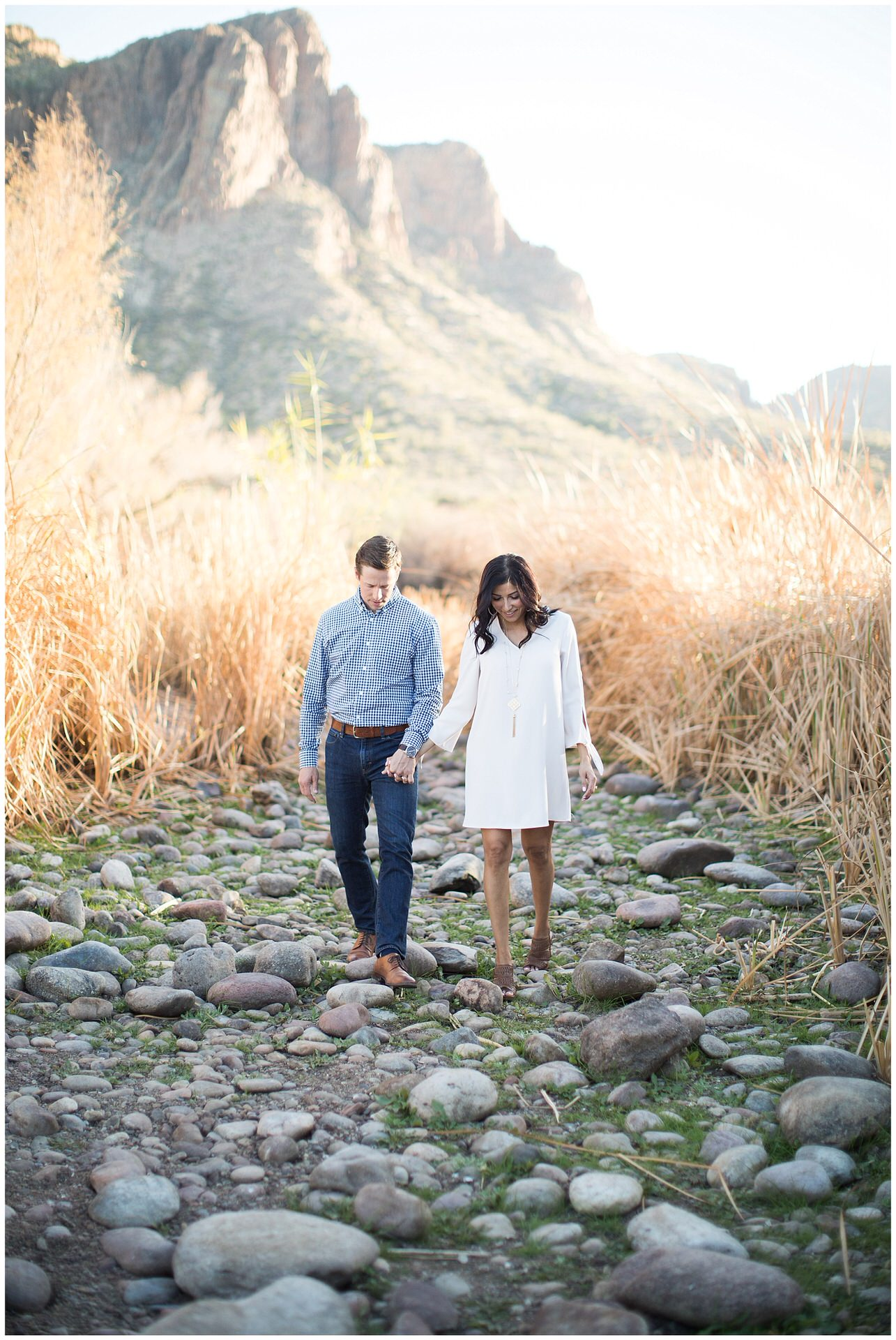 Couple walking along riverbed of the Salt River holding hands with Tonton National Forest in the background