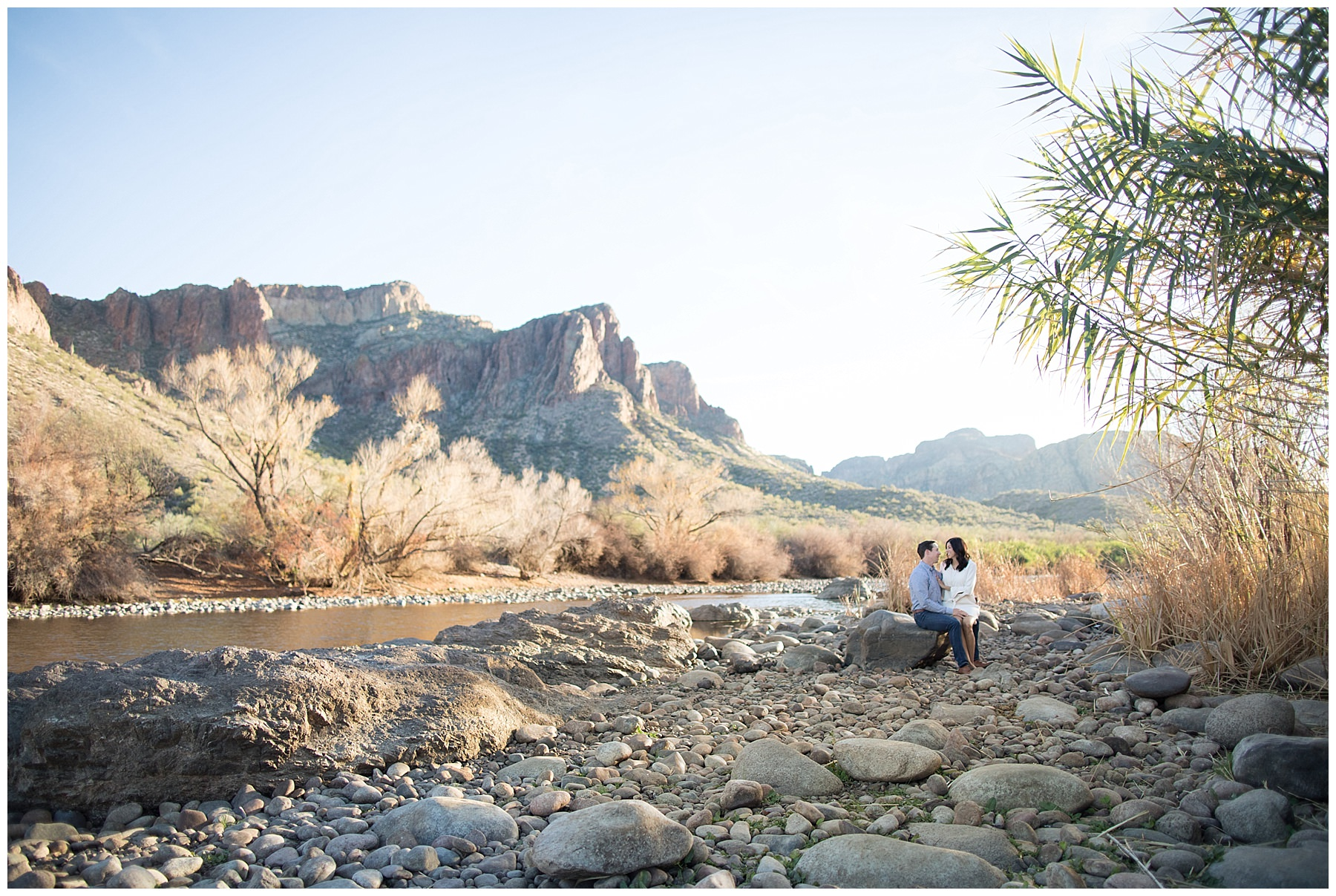 engaged couple sitting on rock at the Salt River