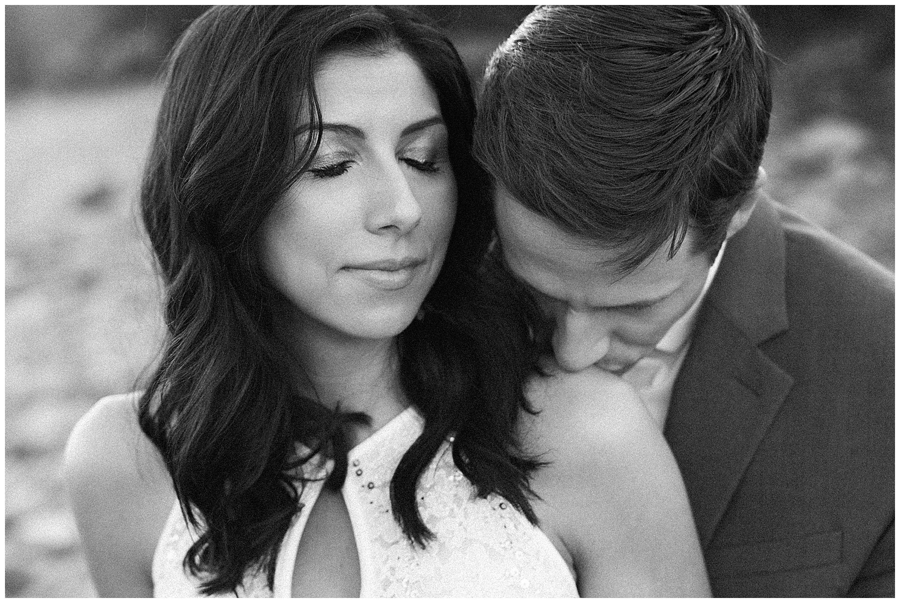 Black and white image of groom kissing brides shoulder