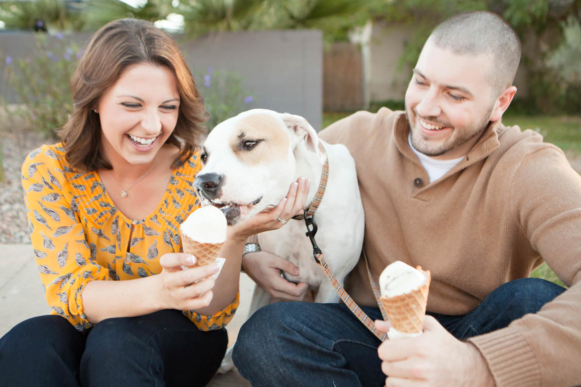 Couple feeding dog ice cream