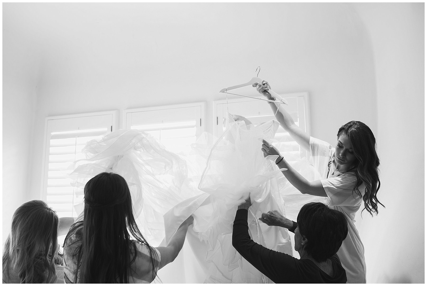 bridesmaids helping wedding dress prepared