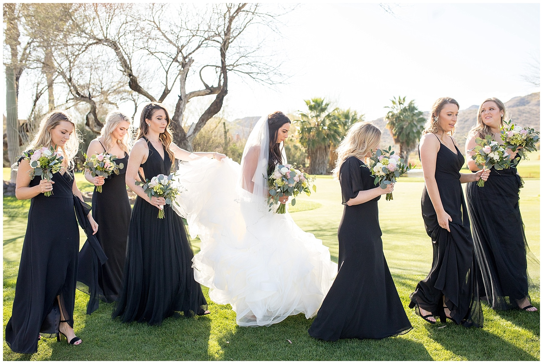 Bridemaids in Black Watters dresses walking with Bride